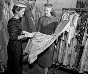 Woman choosing dress in shop