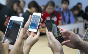 Journalists take pictures of a new Apple iPhone handset with their cellphones during an Apple press conference in Beijing on September 11, 2013. (Photo: AFP/Getty)