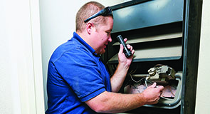 Heater repair technician working on furnace