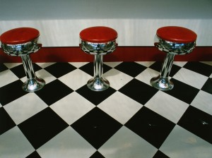 Red stools on a black and white vinyl tile floor (Getty Images/Visions of America)
