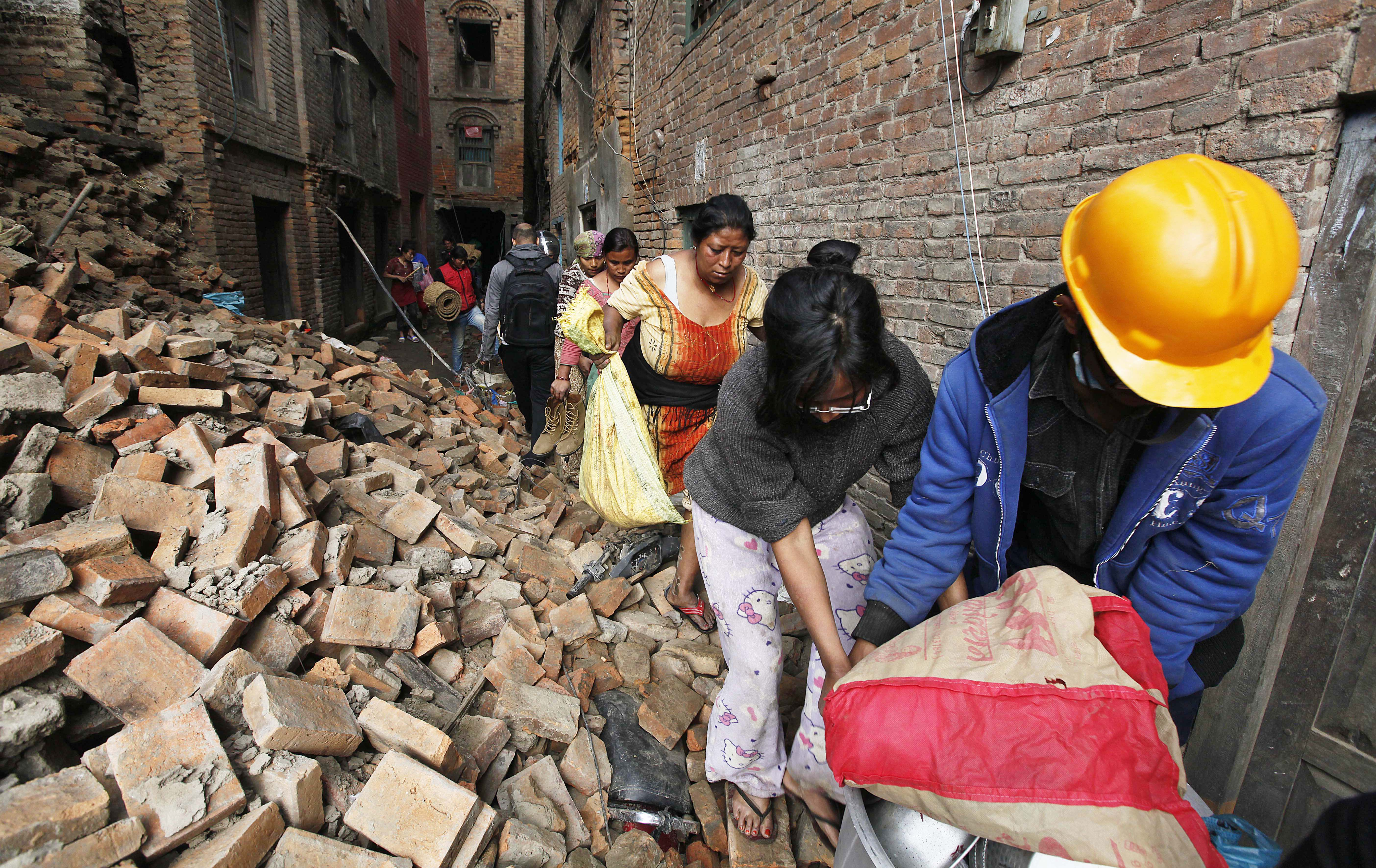 KATHMANDU, NEPAL – APRIL 28: Nepalese people rescue items from the debris of houses damaged in devastating earthquake at Bhaktapur on April 28, 2015 in Kathmandu, Nepal. The death toll from the earthquake rose to over 4,600. Another 72 people died in India, while China reported 25 deaths. Aid groups and at least 16 nations rushed aid and workers to Nepal, with more on the way. (Photo by Raj K Raj/Hindustan Times via Getty Images)