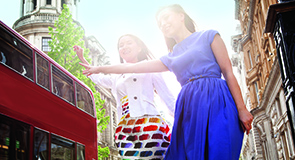 Two young women standing in London street, waving to stop bus
