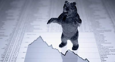 Bear figurine on descending line graph and list of share prices (Adam Gault/Getty Images)