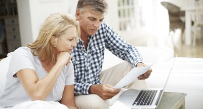 Mature couple doing paperwork and using computer (Musketeer/Getty Images)