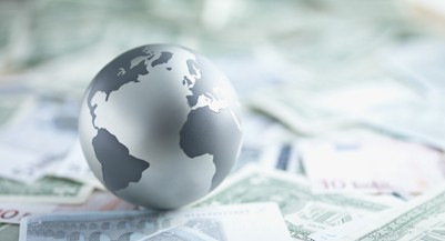 Metal globe resting on paper currency (Martin Barraud/Getty Images)