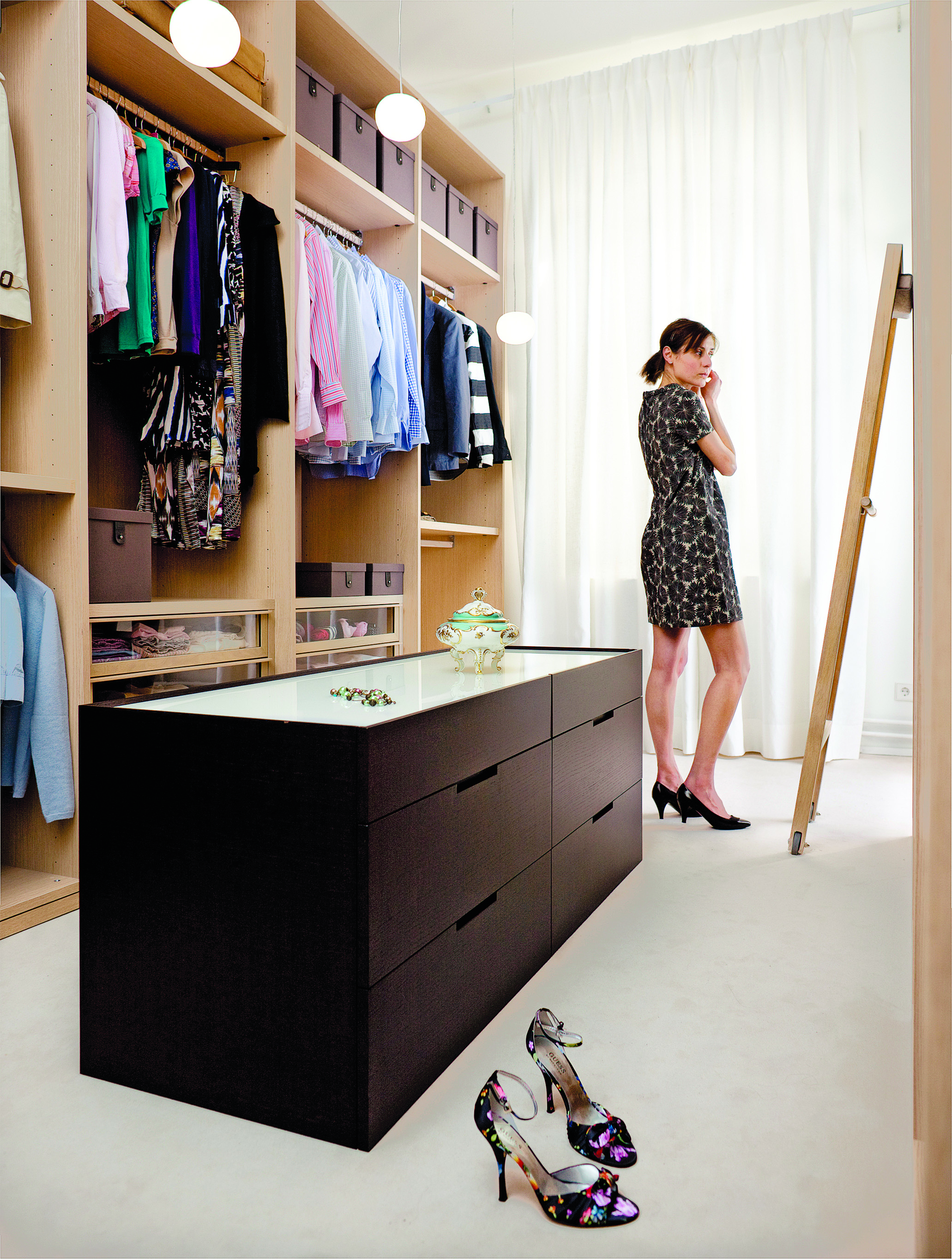 Woman trying clothes in walk-in wardrobe