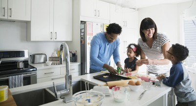 (Hero Images/Getty Images) Family baking cookies in kitchen