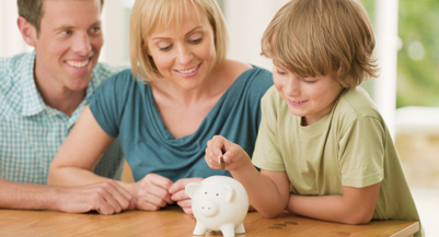 Parents watching son putting coin into piggy bank (Chris Ryan / Getty Images)