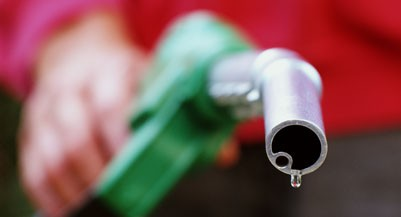 HAND HOLDING GASOLINE NOZZLE (Terry Williams/Getty Images)
