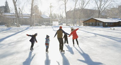 Family ice-skating on outdoor rink together