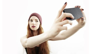 Studio portrait of young woman making selfie on smartphone (JPM/Image Source/Getty images)