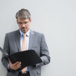 Mature businessman reading paperwork outside office building