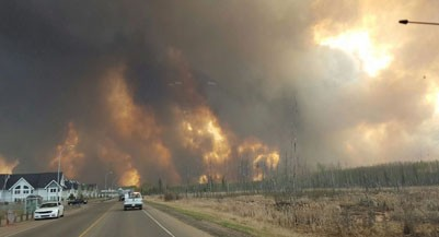 A wall of fire rages outside of Fort McMurray, Alta. Tuesday May 3, 2016 as a wildfire threatened the city. Raging forest fires whipped up by shifting winds sliced through the middle of the remote oilsands hub city of Fort McMurray Tuesday, sending tens of thousands fleeing in both directions and prompting the evacuation of the entire city. THE CANADIAN PRESS/ Mary Anne Sexsmith-Segato