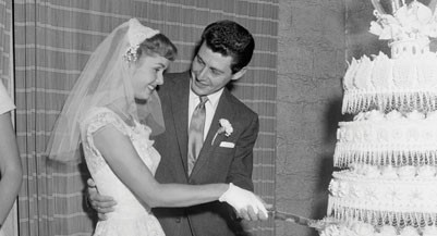 26 Sep 1955, Grossinger, New York State, USA --- Original caption: Happy Ending to Publicized Romance. Grossinger, N.Y.: Debbie Reynolds and Eddie Fisher cut the wedding cake following their marriage tonight at the home of Elaine Grossinger Etess on the grounds of the Grossinger Resort in the Catskills. Their 15 month romance was climaxed by a three minute civil ceremony. After the five foot cake was cut, the couple sipped champagne with intimate friends and relatives, and then slipped off to an undisclosed destination. Their honeymoon will be interrupted tomorrow, however, because Eddie has a singing engagement in Washington, D.C. --- Image by © Bettmann/CORBIS