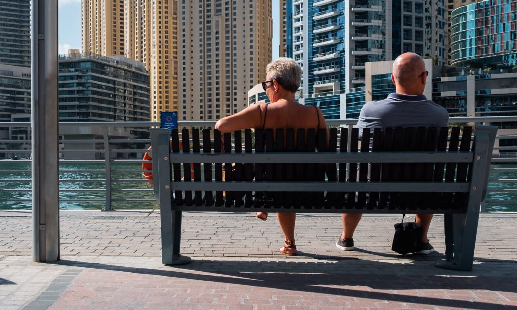 A couple in their mid-50s sits on a bench along the water in front of of condo buildings.