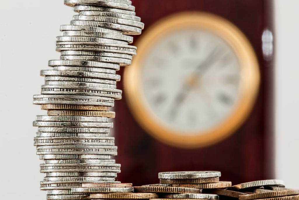 Clock in the background with a stack of coins. Time your earnings to minimize taxes