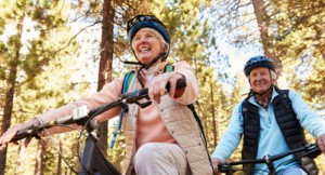Senior couple mountain biking on a forest trail, low angle (iStock/monkeybusinessimages)