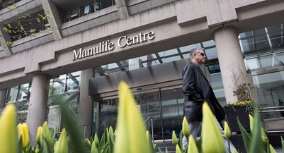 A man walks by the Manulife Centre in Toronto on the day of the Manulife Financial annual general meeting on Thursday, May 3, 2012. Manulife Financial Corp. confirmed Monday its banking unit was penalized last year after Canada's money-laundering watchdog concluded it failed to report a suspicious transaction and various money transfers. THE CANADIAN PRESS/Aaron Vincent Elkaim