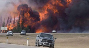 A wild fire rips through the forest 16 kilometres south of Fort McMurray, Alta., on highway 63 on May 7, 2016. International experts say social workers should play a greater role in assisting in natural disasters.The experts are taking part in a University of Calgary workshop with the aim of building a provincewide network of social workers in Alberta ready to assist in the event of natural disasters such as the 2013 floods in southern Alberta or last year's Fort McMurray wildfire. THE CANADIAN PRESS/Jonathan Hayward