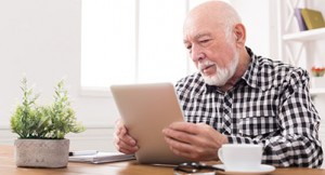 guaranteed income supplement - elderly man looking at digital tablet