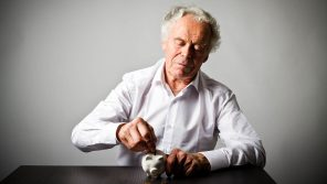 tfsa for retirement. older man putting money into piggy bank