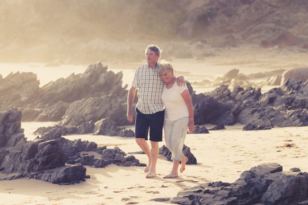 Reducing-taxes-in-retirement-couple-walks-on-beach-Zolo