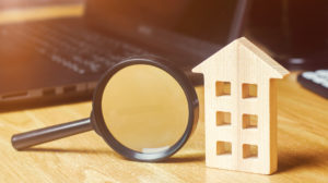 Wooden-house-magnifying-glass-capital-gains-tax-strategies-RKHomeowner