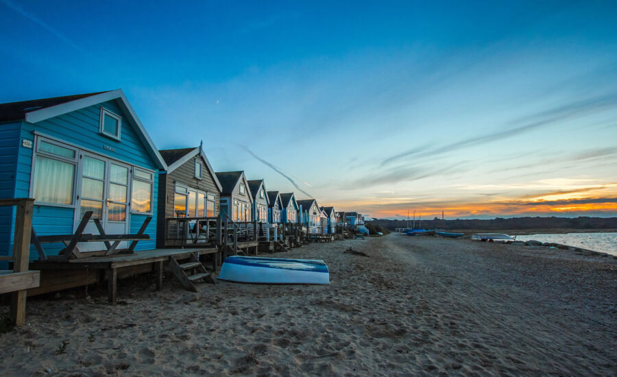 A beach front view of a row of cottages