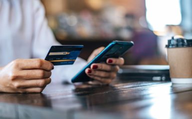 a woman holding a debit card and a phone