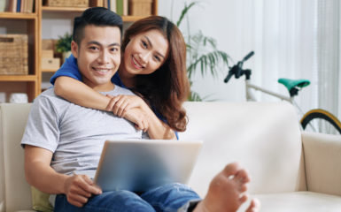 Smiling couple with laptop