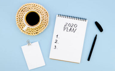 Cup of coffee, pen and pad of paper, with a list of 2020 to-dos