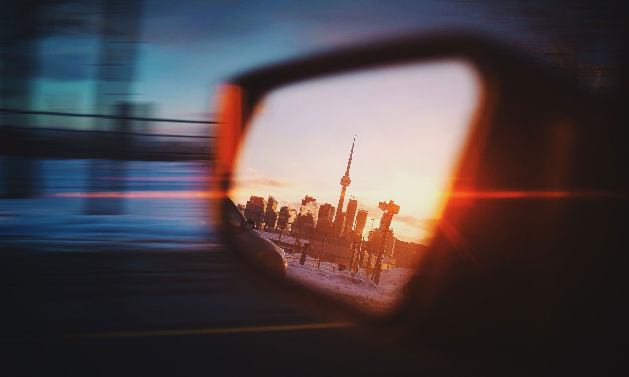 Review mirror showing the city scape of Toronto with the CN Tower at the peak