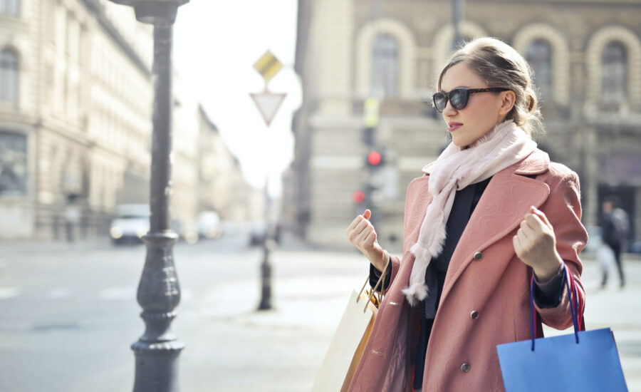 well dressed woman on a street holding shopping bags