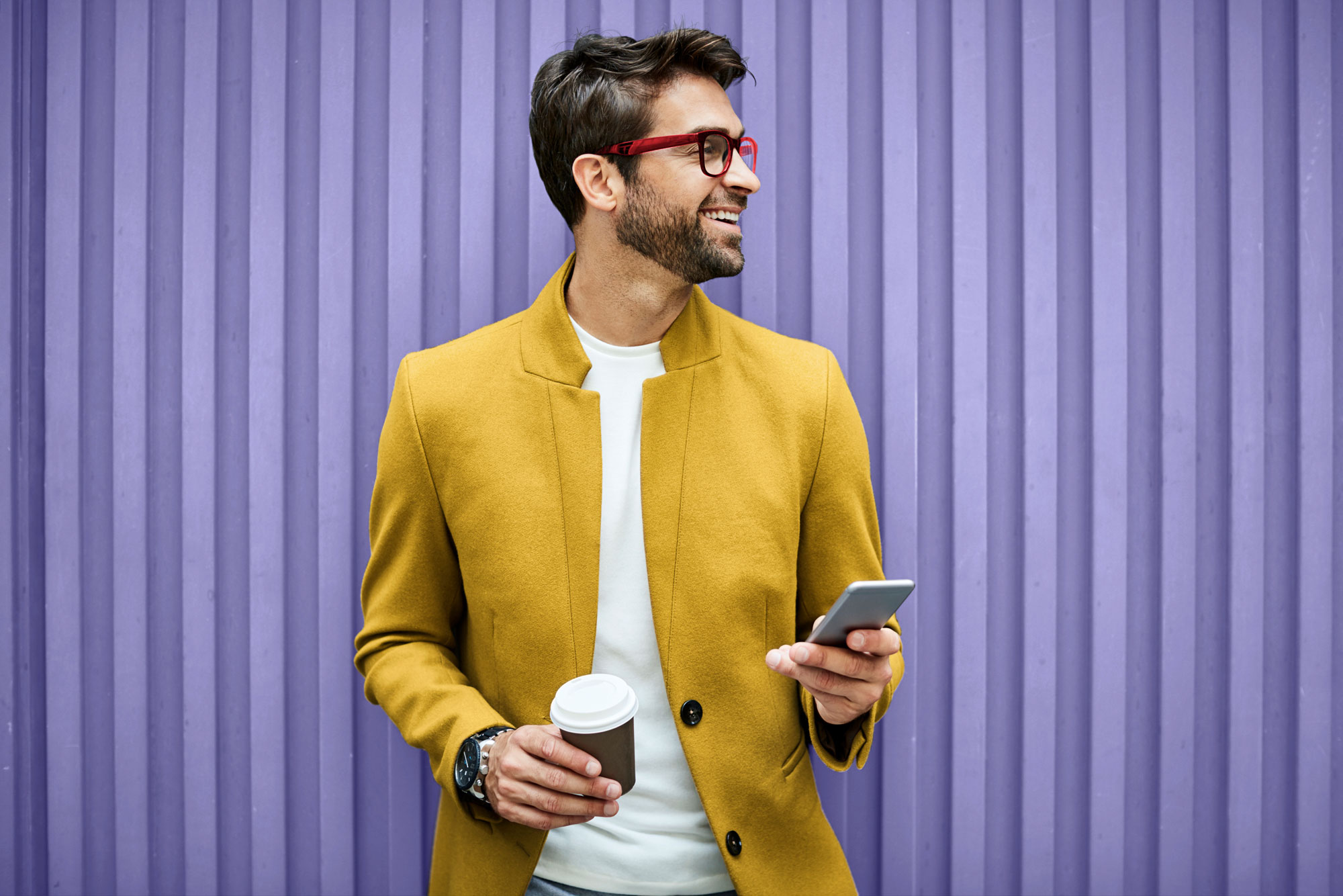 man smiling as he's using his phone and having a coffee