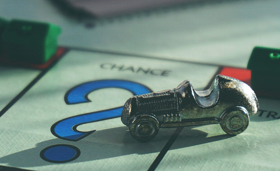 Monopoly car game piece on top of the question mark on the Monopoly board.