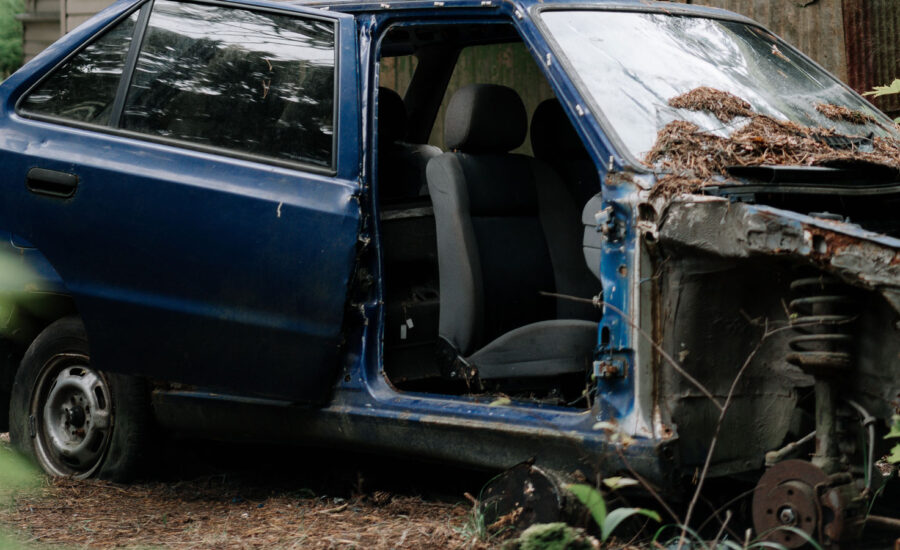 An abandoned car with smashed windows and a door ripped off