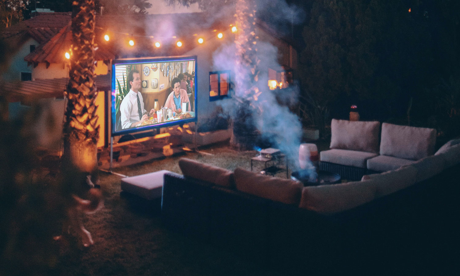The ultimate backyard fire pit, surrounded by an outdoor sectional sofa and a big movie screen