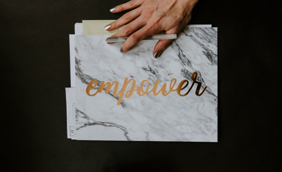 hand on a folder that reads empower, as in these tips will empower you when doing your taxes!