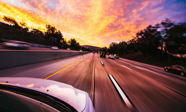 A car driving toward a sunset