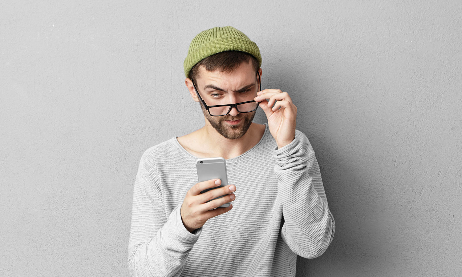 A man lowering his glasses to read a message on his phone