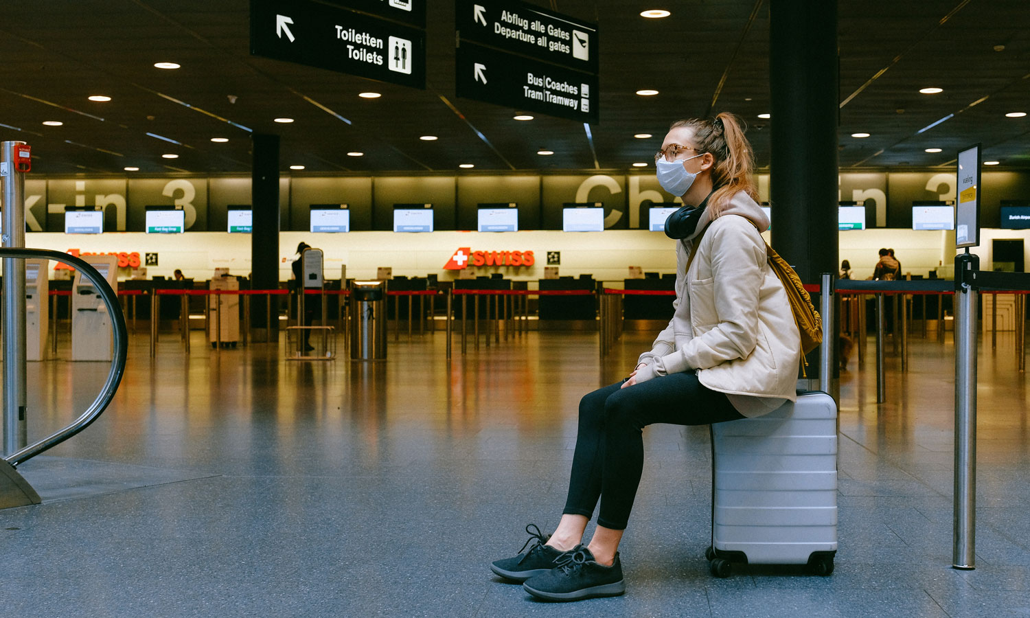A woman wearing a mask, while sitting on a suitcase waiting for her flight gate to be announced.