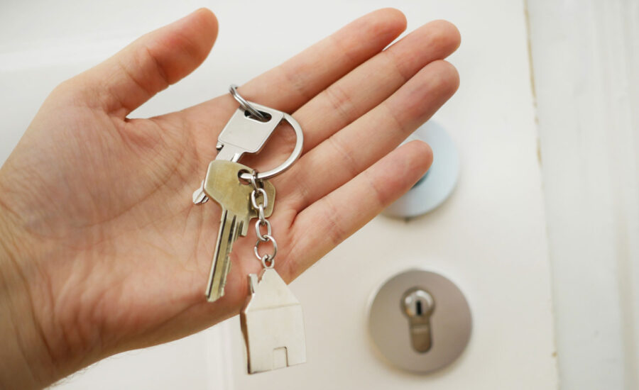 A hand holding different keys with a house keychain