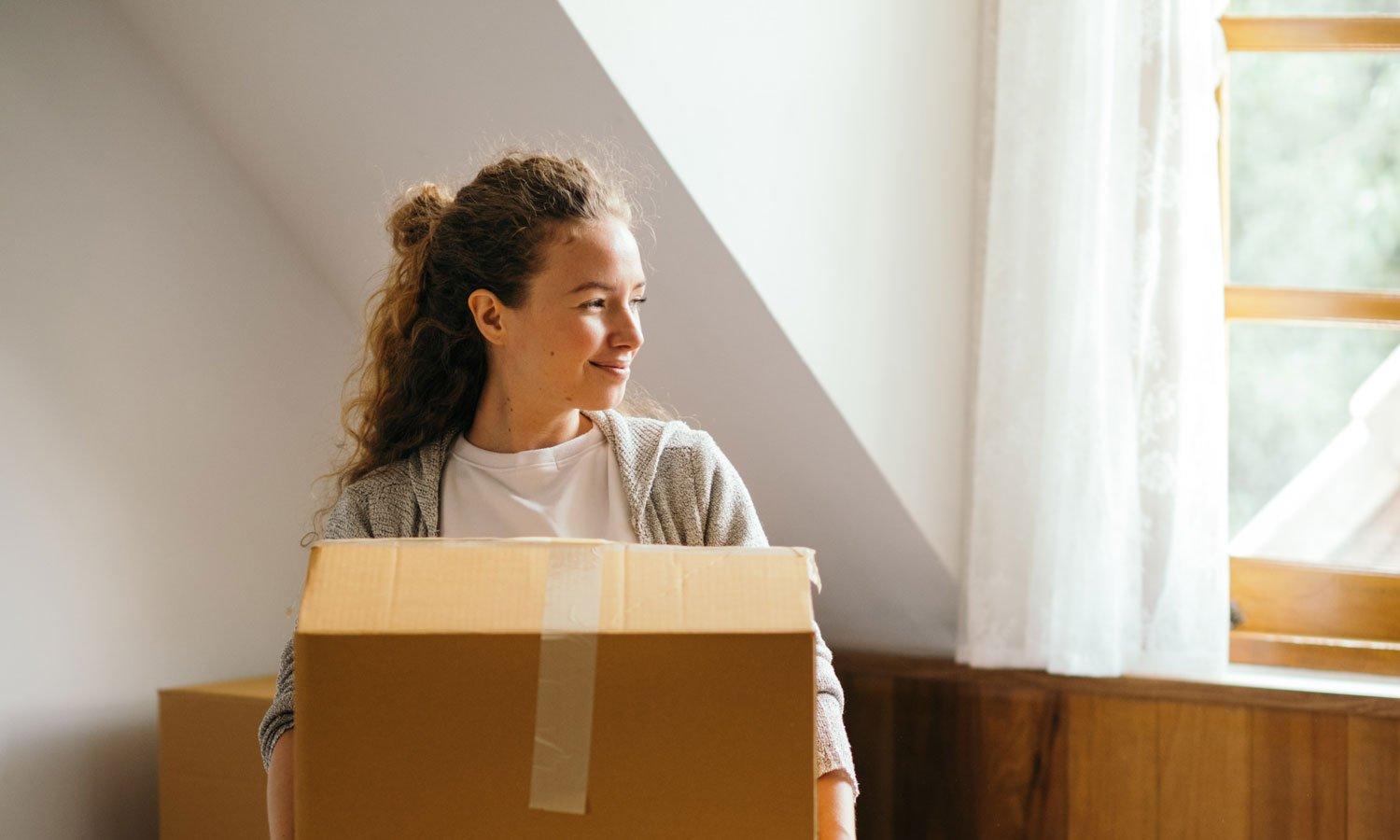 A woman holding a box as she moves into her first apartment