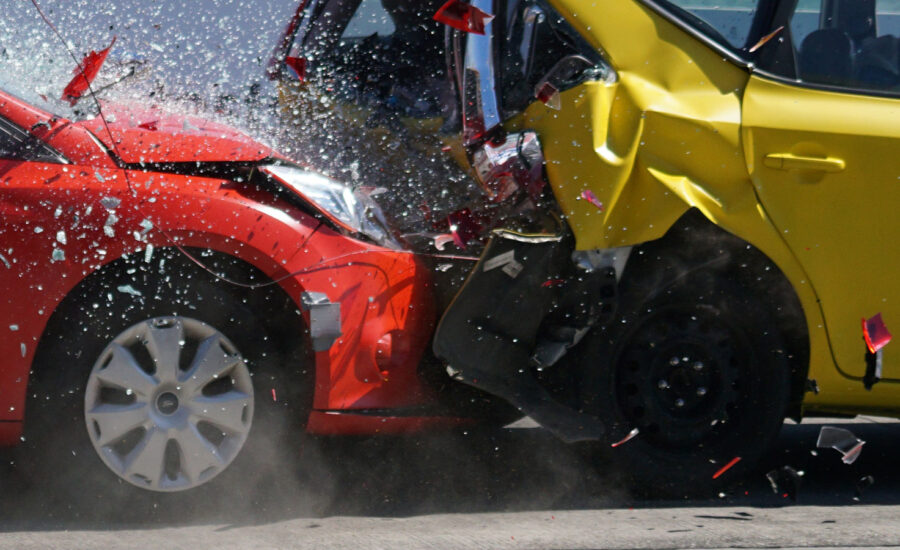 Two cars in the middle of a car accident. One car is rear-ending another with glass shattering into the air