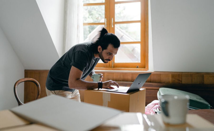 A man at home, scrolling his computer for the best TFSA rates
