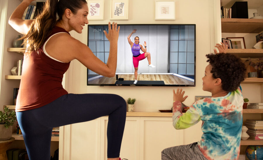 A woman doing a workout with her son, using the Peloton app. They're laughing because working out is fun, no?