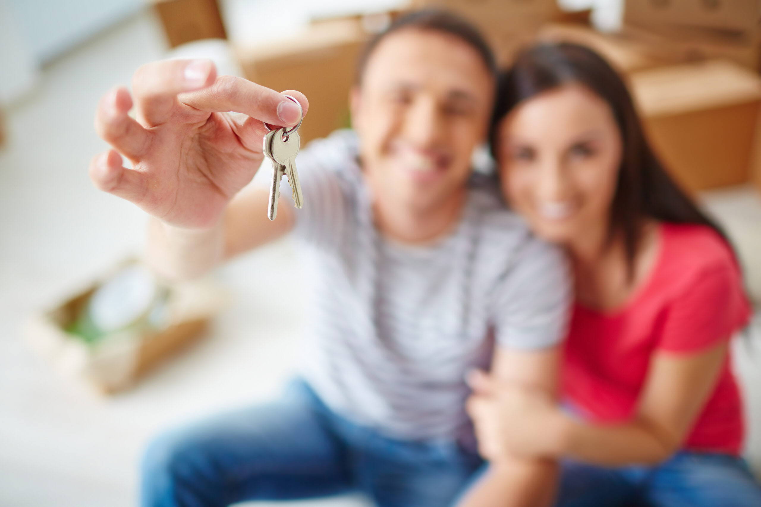 Close-up of man's hand holding house keys with soft focus couple in background
