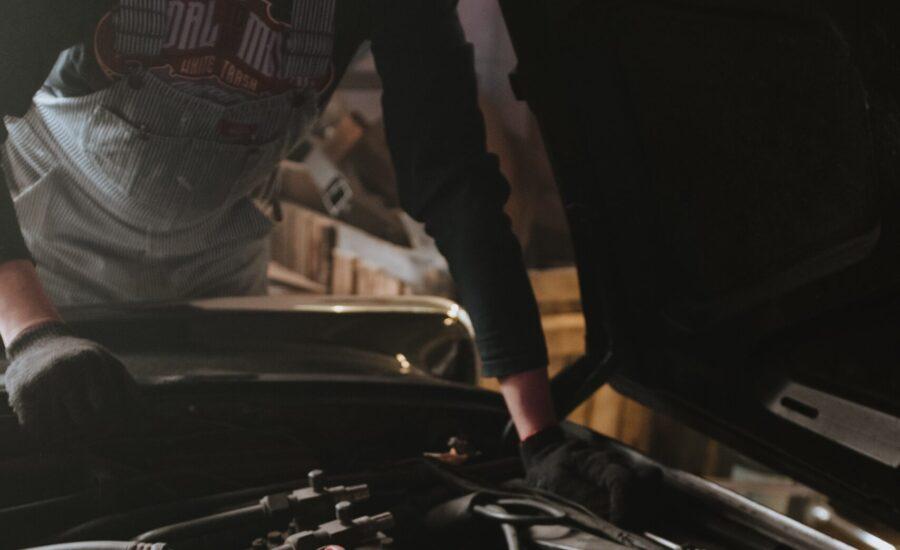 car owner looking under hood at engine