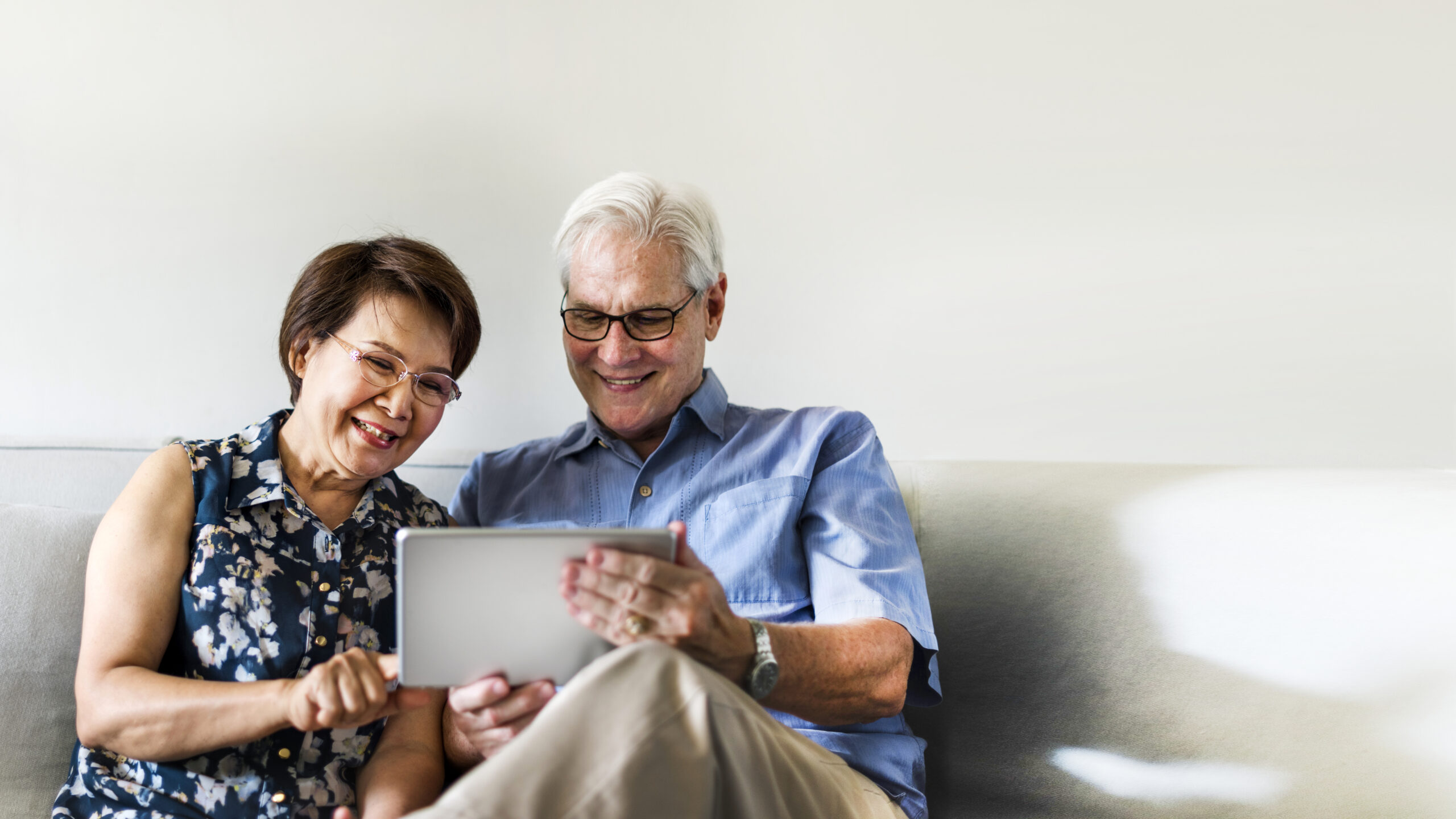 Senior couple using a digital device in a living room