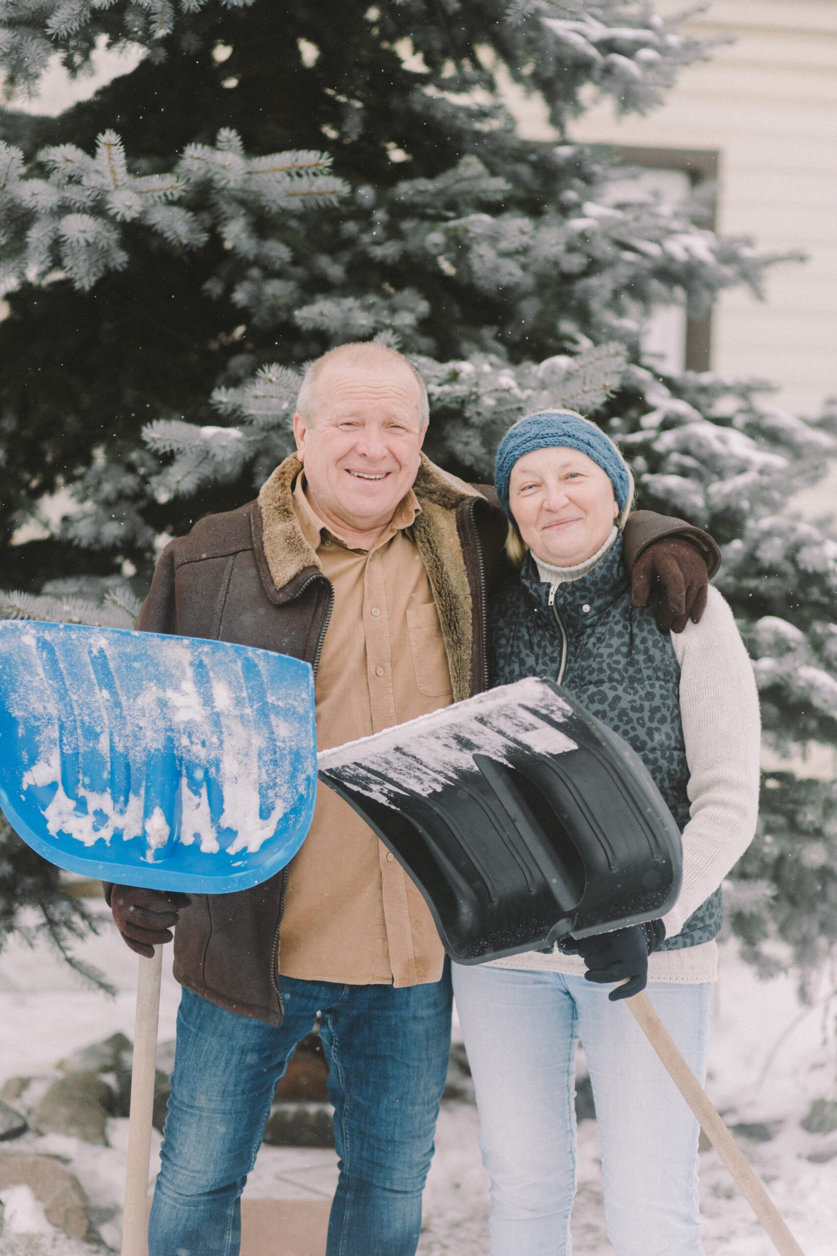 senior couple shovelling snow outside their home